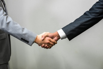 White man in a suit shaking hands with Hispanic man in a suit, wide