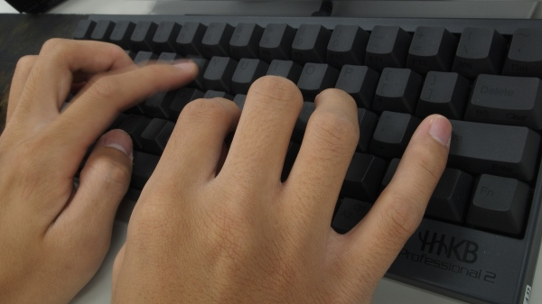 Man typing on computer keyboard.