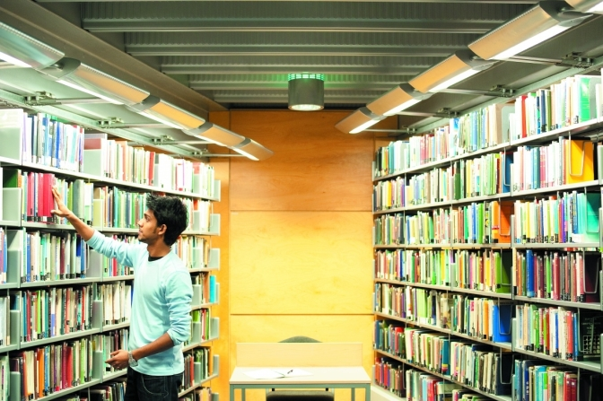 Male undergraduate student reaching for a book in the Learning Resource Centre, Jubilee Campus
