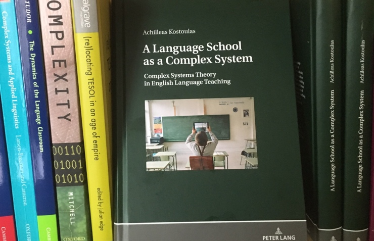 Photo of the book, A Language School as a Complex System, among other books on a shelp
