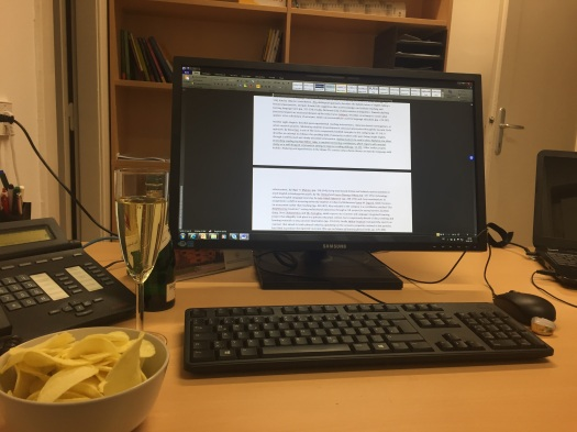 Computer, flanked by telephone, laptop, wine glass and potato chips.