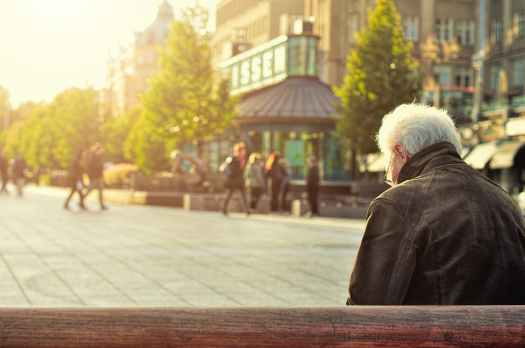 Older man sitting on wooden bench, with young people in the background